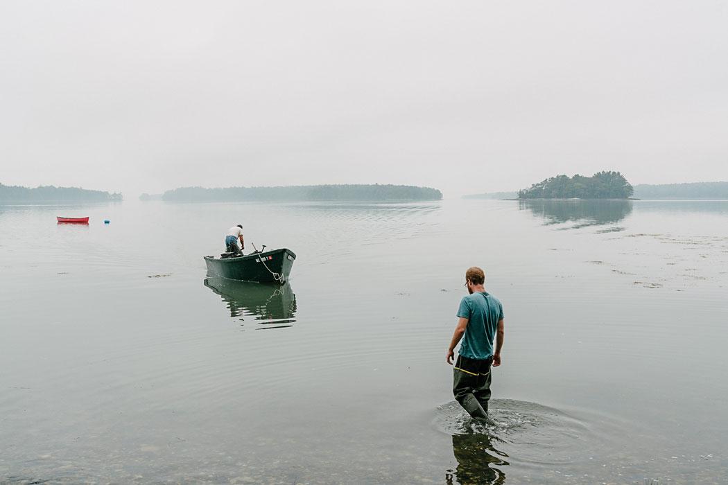 man walking in water to boat