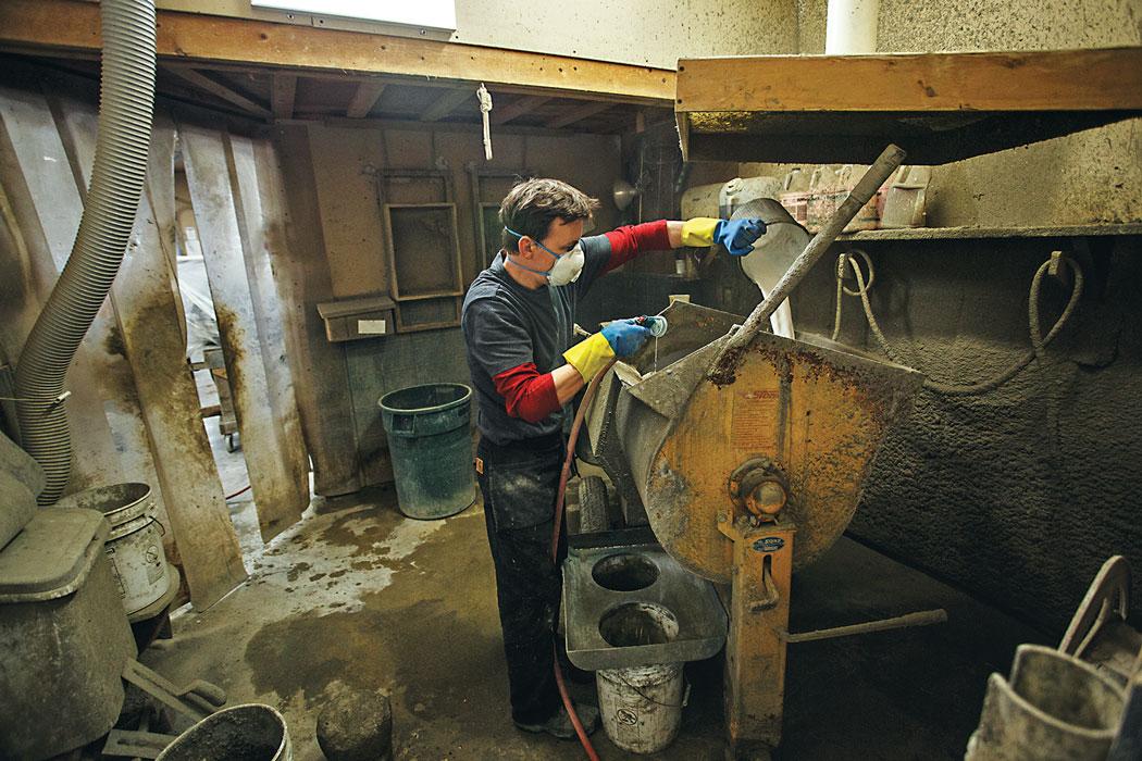 man pouring concrete into mold