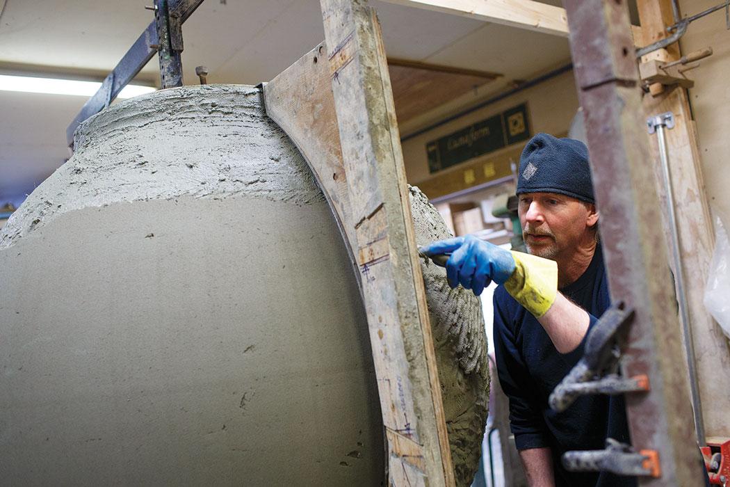 man working on large urn
