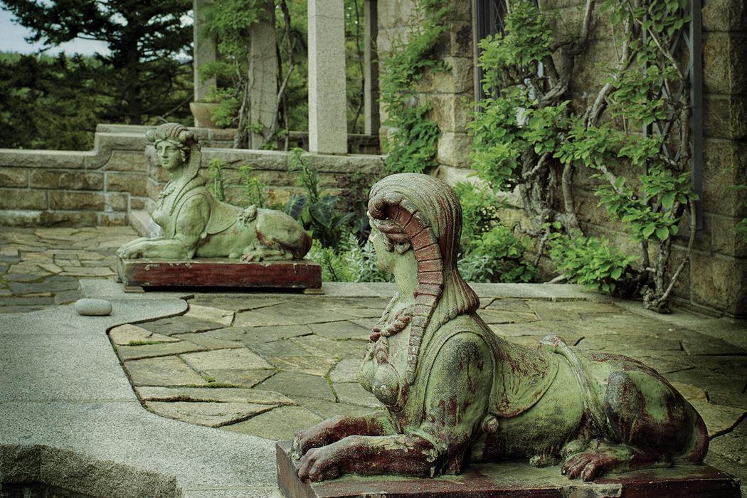 half woman half animal statues outside the house