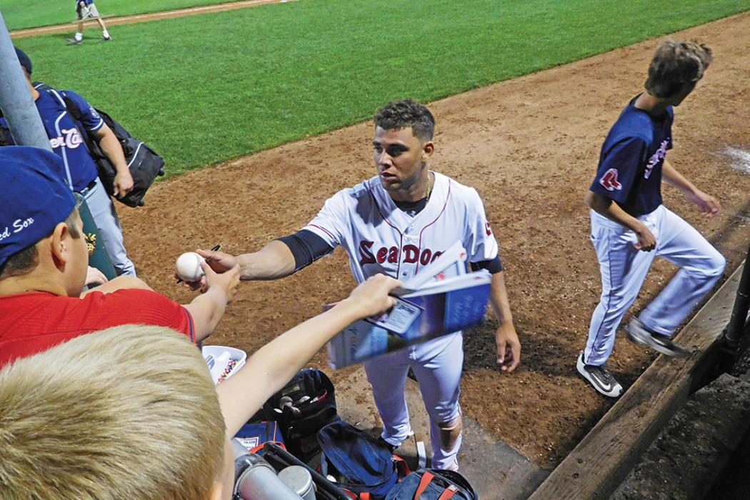 baseball player giving ball to crowd